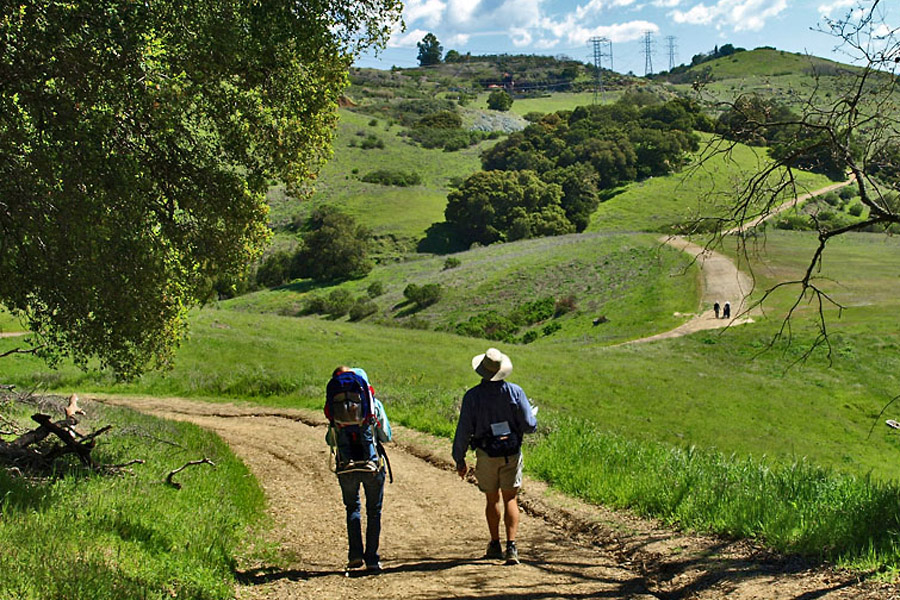 hikers hiking up a trail through the rolling green hills of Almaden quicksilver