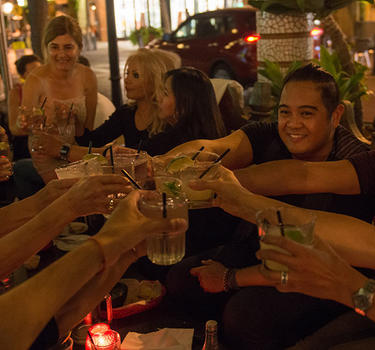 A group enjoying happy hour and dinner outdoors at El Jardin Tequila Bar