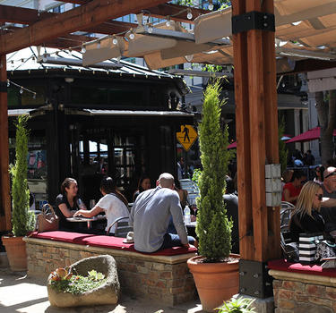 View of a full patio at Vintage Wine Bar and the unique wine bar room in the background