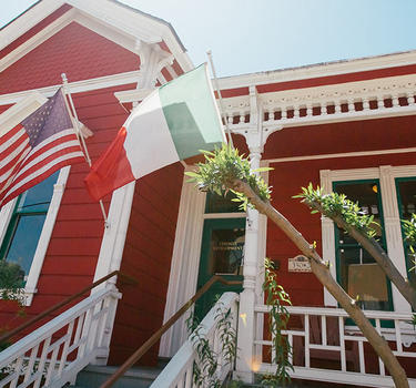 An immaculate, red and white Victorian home with the American and Italian flags flying in Little Italy.