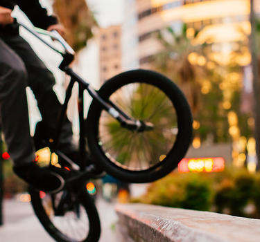 A guy on a bmx bike doing a trick on a cement block with buildings and palm trees in the background
