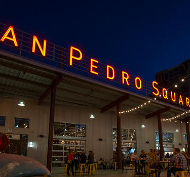 People mingling and dining on the front patio under the lit San Pedro Square Market sign