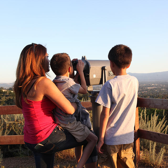 A family viewing San Jose and Silicon Valley from a telescope on a trailhead lookout at Alum Rock Park
