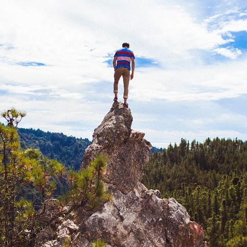 A hiker standing on top of a mountain peak overlooking the gorgeous redwood draped Big Basin Redwoods State Park