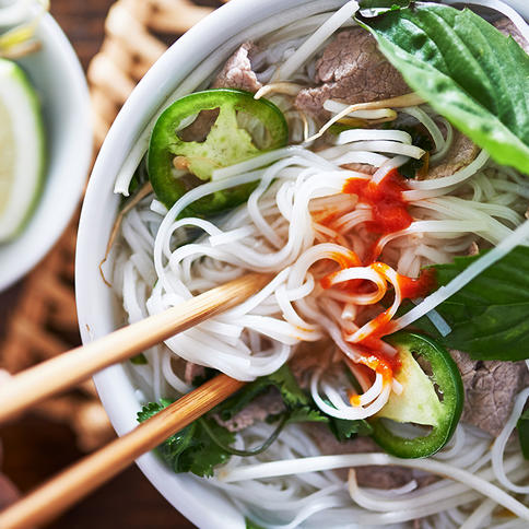 Close-up of bowl of Asian food with chopsticks