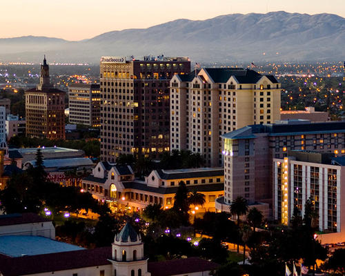Image of downtown San Jose at twilight with the beautiful golden rolling hills of Mount Diablo