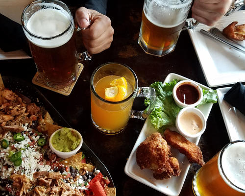 Table filled with different foods and glasses of beer.