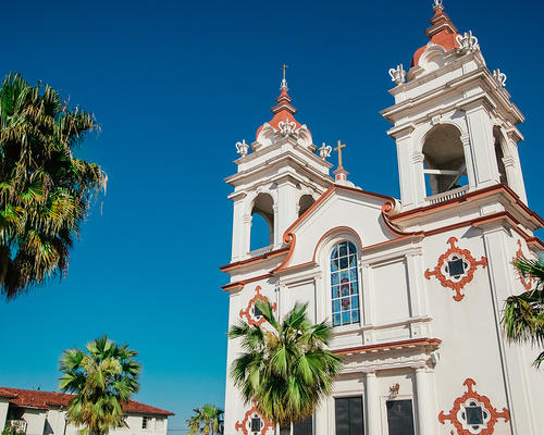Beautiful Spanish style church surrounded by palm trees.