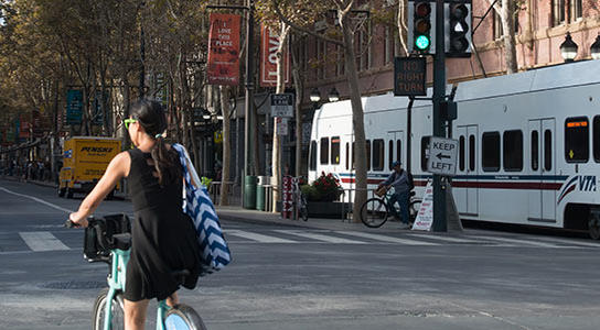 A girl passes on bike share with VTA light rail moving across Santa Clara street in downtown San Jose