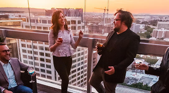 people have drinks on a balcony