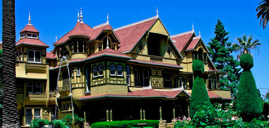 Exterior of the Winchester Mystery House featuring the beautiful gardens and fountain in front.