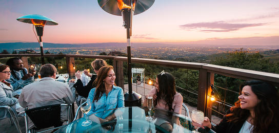 Group dining on the pation of GrandView Restaurant at dusk overlooking the city lights of Silicon Valley