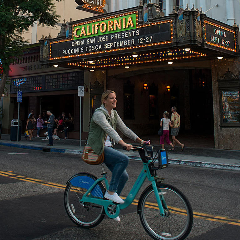 Woman riding Ford GoBike in front of California Theatre