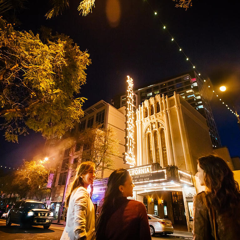 Women standing in front of the California Theatre at night