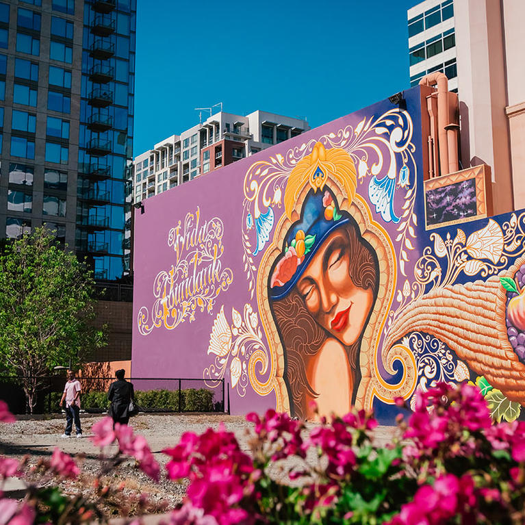 The colorful Vida Abundant mural, a woman with cornucopia, painted on the side of Hotel De Anza