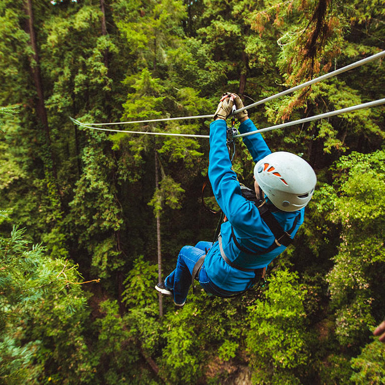 A woman ziplines through the redwoods at Mount Herman Adventures in Felton