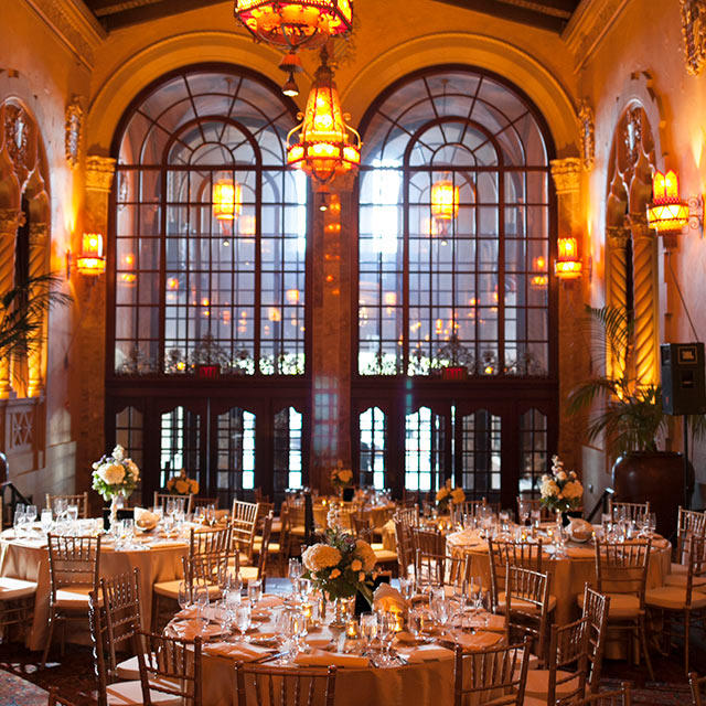 The gold embellished lobby of the historic California Theatre set for an elegant sit-down dinner