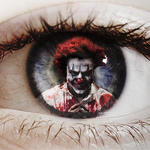 Scary clown superimposed on the iris of a closeup eye