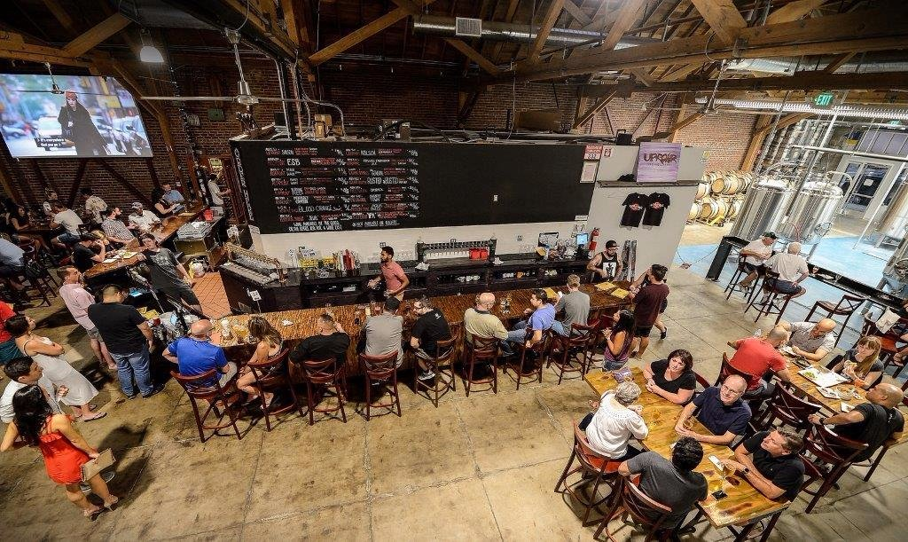 people enjoying food and beer at Uproar Brewery